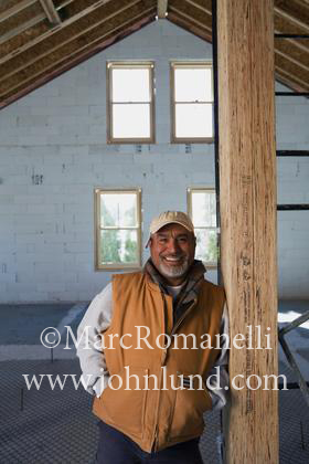 Stock Photo of a hispanic contractor on the job site. He is wearing a vest and a baseball cap. He has a beard and is smiling and happy.